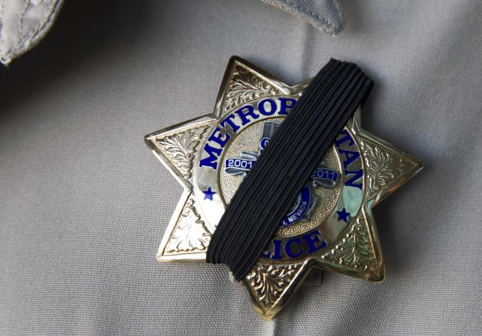 A Metro Police officer wears a ribbon over his badge at Metro headquarters as police mourn for two slain officers in Las Vegas June 8, 2014. Two suspects, also dead, shot two Metro Police officers in a pizza shop then fled to a nearby Wal-Mart where they shot and killed another person, police said. REUTERS/Las Vegas Sun/Steve Marcus (UNITED STATES - Tags: CIVIL UNREST CRIME LAW)