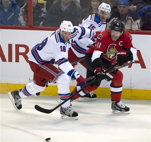 Ottawa Senators right wing Daniel Alfredsson passes the puck under pressure from New York Rangers defenseman Marc Staal (left) and Jeff Halpern (15) during first period NHL action in Ottawa on Thursday February 21, 2013. THE CANADIAN PRESS/Adrian Wyldduring the first period of an NHL hockey game in Ottawa, Ontario, Thursday, Feb. 21, 2013. (AP Photo/The Canadian Press, Adrian Wyld)