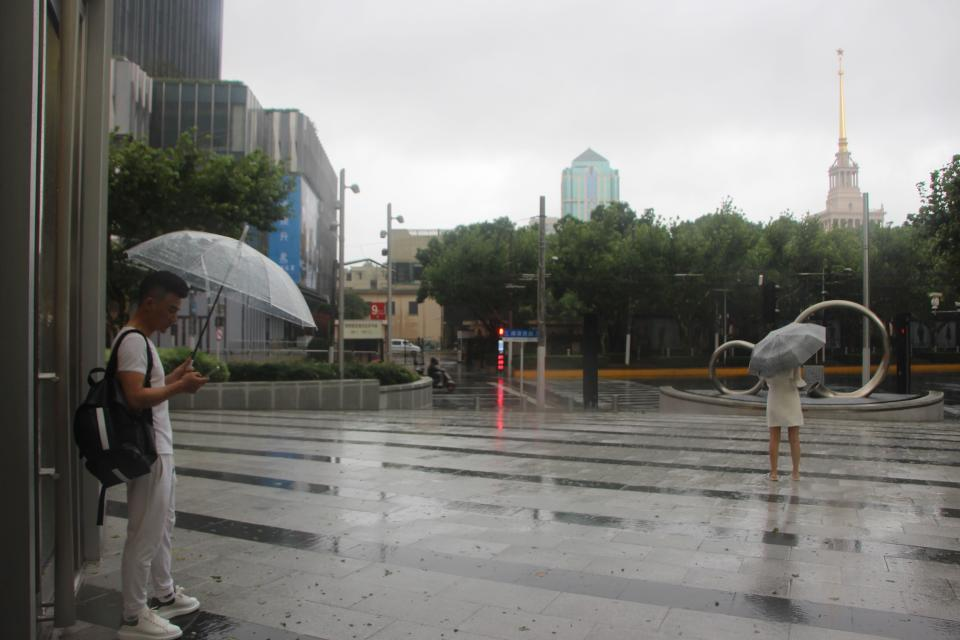 Residents stand with umbrellas in the rain as Typhoon In-fa sweeps through Shanghai in China Sunday, July 25, 2021. Typhoon In-fa hit China's east coast south of Shanghai on Sunday after people living near the sea were evacuated, airline flights and trains were canceled and the public was ordered to stay indoors. (AP Photo/Chen Si)