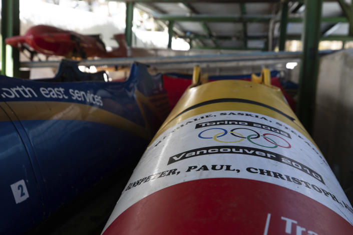 Bobsleds are stored next to the course in Cortina d'Ampezzo, Italy, Wednesday, Feb. 17, 2021. Bobsledding tradition in Cortina goes back nearly a century and locals are hoping that the Eugenio Monti track can be reopened for the 2026 Olympics in the Italian resort. (AP Photo/Gabriele Facciotti)