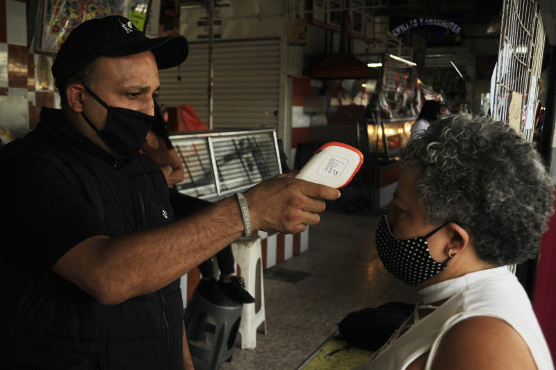 MEXICO CITY, MEXICO - MAY 19, 2020: A Man wears face mask while check the temperature to a woman before she entering at Martinez de la Torre Market as preventive measure. On May 19, 2020 In Mexico City, Mexico- PHOTOGRAPH BY Ricardo Castelan Cruz / Eyepix Group / Barcroft Studios / Future Publishing (Photo credit should read Ricardo Castelan Cruz / Eyepix Group/Barcroft Media via Getty Images)