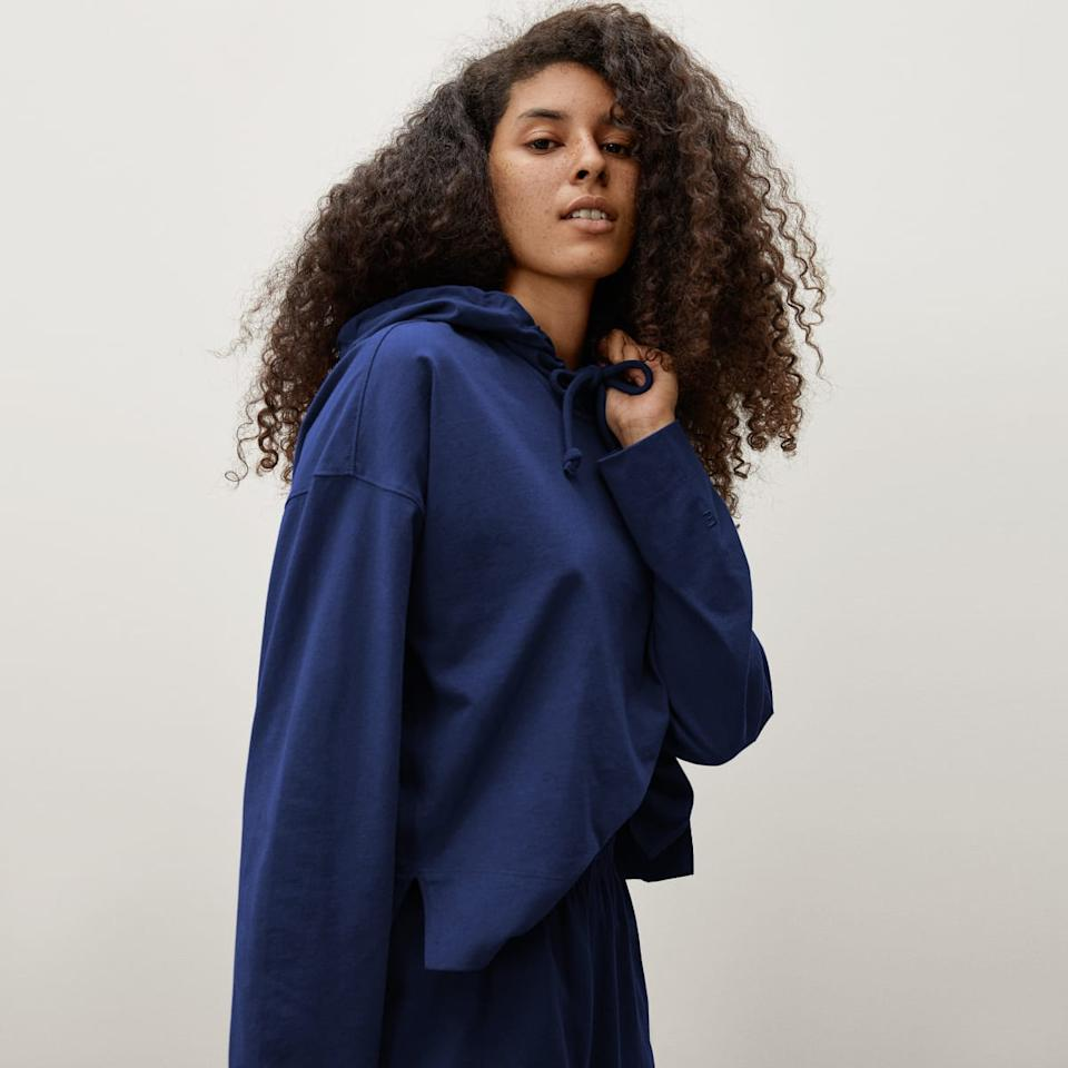 Model wears  The Retro Jersey Hoodie in blue with matching joggers. Image via Everlane.