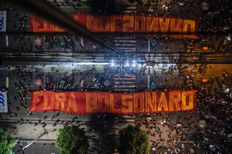 "A giant banner reading ""Get Out Bolsonaro"" is displayed during a strike to protest proposed pension reforms"