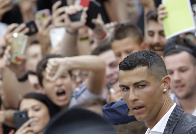 RETRANSMISSION OF XLB104 TO PROVIDE DIFFERENT CROP - Portuguese ace Ronaldo passes among enthusiast fans as he arrives to undergo medical checks at the Juventus stadium in Turin, Italy, Monday, July 16, 2018. (AP Photo/Luca Bruno)