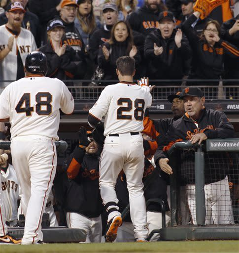 San Francisco Giants' Buster Posey (28) is greeted at the dugout after hitting a two-run home run against the Atlanta Braves during the third inning of a baseball game, Thursday, May 9, 2013, in San Francisco. At left is Giants' Pablo Sandoval (48). (AP Photo/George Nikitin)