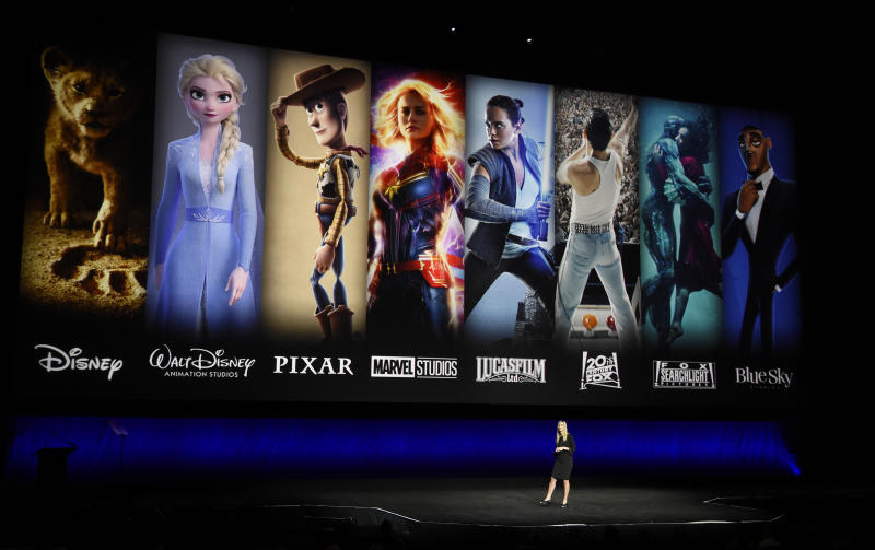 FILE - In this April 3, 2019, file photo characters from Disney and Fox movies are displayed behind Cathleen Taff, president of distribution, franchise management, business and audience insight for Walt Disney Studios during the Walt Disney Studios Motion Pictures presentation at CinemaCon 2019, the official convention of the National Association of Theatre Owners (NATO) at Caesars Palace in Las Vegas. On Tuesday, Nov. 12, Disney Plus launches its streaming service. (Photo by Chris Pizzello/Invision/AP, File)