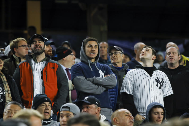 Fans watch during the fifth inning in Game 4 of baseball's American League Championship Series between the Houston Astros and the New York Yankees Thursday, Oct. 17, 2019, in New York. (AP Photo/Matt Slocum)