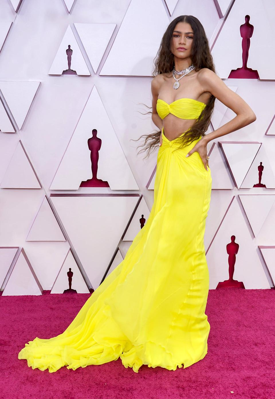 """<p><a href=""""https://www.popsugar.com/fashion/zendaya-yellow-valentino-oscars-dress-2021-48288757"""" class=""""link rapid-noclick-resp"""" rel=""""nofollow noopener"""" target=""""_blank"""" data-ylk=""""slk:Zendaya's 2021 Oscars gown"""">Zendaya's 2021 Oscars gown</a>, created by Valentino, not only glowed in the dark, but was an homage to Cher's cutout <a href=""""https://www.vogue.com/article/zendaya-oscars-valentino-dress-cher-reference"""" class=""""link rapid-noclick-resp"""" rel=""""nofollow noopener"""" target=""""_blank"""" data-ylk=""""slk:look from The Sonny and Cher Show"""">look from <strong>The Sonny and Cher Show</strong></a> in the 1970s. """"All that custom Bob Mackie that she owned, I want all of that. Cher, if you ever want to style me, Law [Roach] and I would love it,"""" <a class=""""link rapid-noclick-resp"""" href=""""https://www.popsugar.com/Zendaya"""" rel=""""nofollow noopener"""" target=""""_blank"""" data-ylk=""""slk:Zendaya"""">Zendaya</a> said, deeming the star her fashion icon. In fact, <a href=""""https://www.popsugar.com/fashion/zendaya-referencing-celebrities-on-the-red-carpet-48397285#photo-48397375"""" class=""""link rapid-noclick-resp"""" rel=""""nofollow noopener"""" target=""""_blank"""" data-ylk=""""slk:Cher also wore a yellow Bob Mackie two-piece"""">Cher also wore a yellow Bob Mackie two-piece</a> to the Oscars in 1973!</p>"""