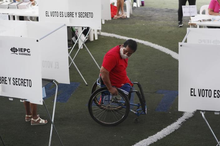 A voter looks for his at booth at a polling station during mid-term elections in Acapulco, Mexico, Sunday, June 6, 2021. Mexicans are elected the entire lower house of Congress, almost half the country's governors and most mayors on Sunday. (AP Photo/Fernando Llano)
