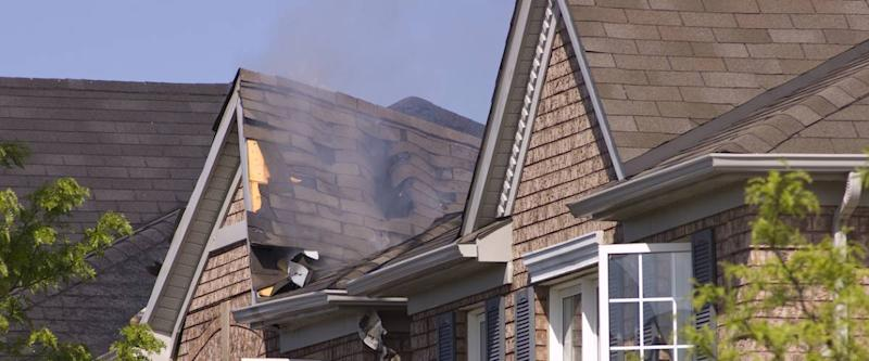 Fire damaged smoldering roof of a nondescript brick house.