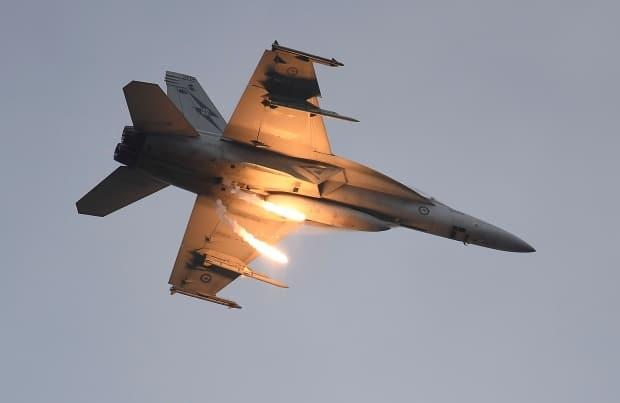 A Royal Australian Air Force  (RAAF) F/A-18F Super Hornet  drops two flares as it performs during the T150 Defence Force Air Show on October 15, 2016, in Townsville, Australia. Boeing's military division was on track to sell the Royal Canadian Air Force a handful of Super Hornet jet fighters in 2017, but the deal went sideways.  (Ian Hitchcock/Getty Images - image credit)