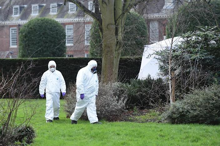Forensics officers in overalls and masks walk past a tent erected over the spot where a man died after being discovered on fire in the park outside the wall of Kensington Palace, central London on February 9, 2016 (AFP Photo/Leon Neal)