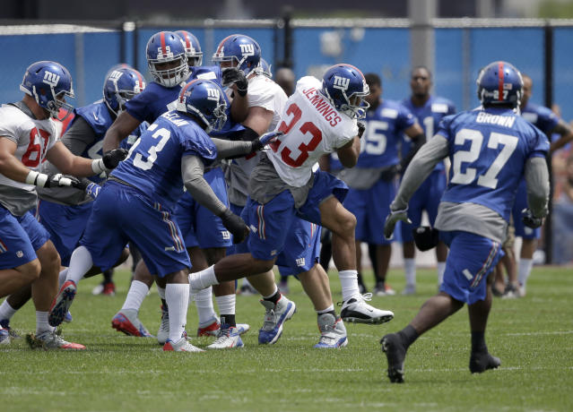 New York Giants' Rashad Jennings (23), center, runs through traffic during NFL football camp in East Rutherford, N.J., Thursday, July 24, 2014. (AP Photo/Seth Wenig)
