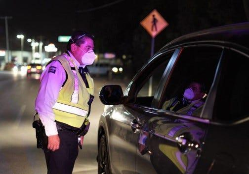 A Juárez traffic officer inspects a vehicle. A nightly curfew and a two-adults-per-vehicle limit were implemented in the Mexico border city on Oct. 23, 2020, in an attempt to curb the spread of COVID-19.