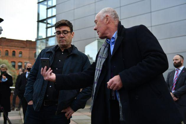 Greater Manchester mayor Andy Burnham (left) with leader of Manchester City Council Sir Richard showing him when the measures will come into force after speaking to the media outside Bridgewater Hall, Manchester.