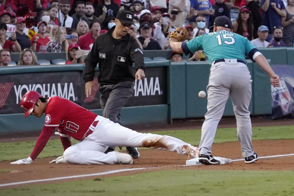 Los Angeles Angels designated hitter Shohei Ohtani, left, is safe at third for an RBI triple as Seattle Mariners third baseman Kyle Seager, right, drops the ball during the first inning of a baseball game Saturday, Sept. 25, 2021, in Anaheim, Calif. (AP Photo/Mark J. Terrill)