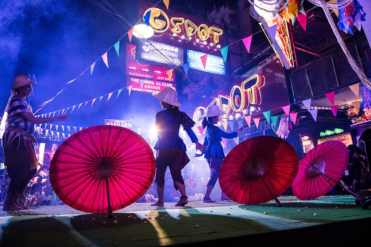 <p>Performers dance on a stage set up in a red light district of Pattaya, at an event used to highlight a push by the town to promote safety in the area. (Photo: Roberto Schmidt/AFP/Getty Images) </p>