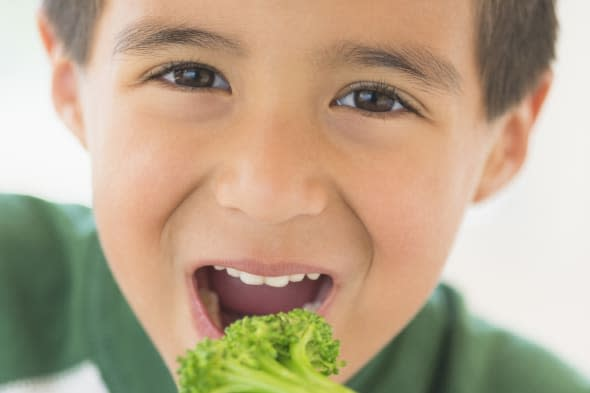 Portrait of boy (6-7) eating broccoli