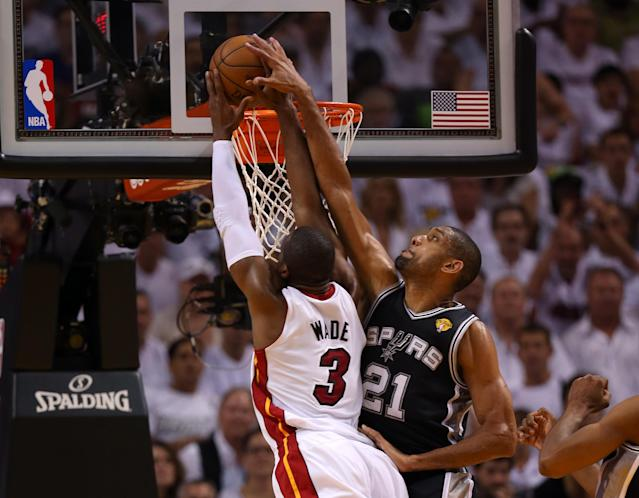 MIAMI, FL - JUNE 18: Dwyane Wade #3 of the Miami Heat goes up for a dunk over Tim Duncan #21 of the San Antonio Spurs in the first quarter during Game Six of the 2013 NBA Finals at AmericanAirlines Arena on June 18, 2013 in Miami, Florida. NOTE TO USER: User expressly acknowledges and agrees that, by downloading and or using this photograph, User is consenting to the terms and conditions of the Getty Images License Agreement. (Photo by Mike Ehrmann/Getty Images)