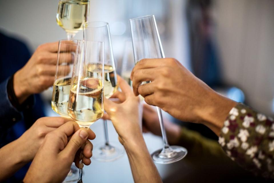 A group of friends cheers glasses of champagne.