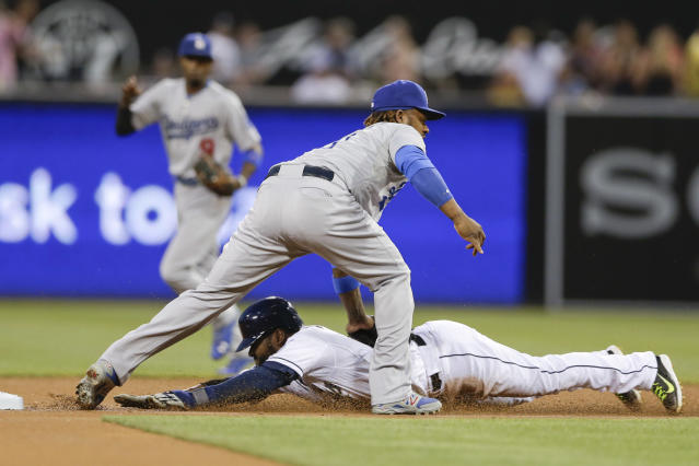 Los Angeles Dodgers shortstop Hanley Ramirez, top, tags out San Diego Padres' Abraham Almonte who slides in late while trying to steal second base during the first inning in a baseball game Friday, Aug. 29, 2014, in San Diego. (AP Photo/Gregory Bull)