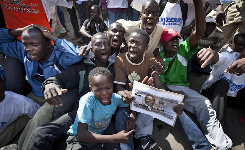 Supporters of losing presidential candidate Raila Odinga hold posters designed as banknotes with his face on, as they protest the verdict of the Supreme Court in Nairobi, Kenya, Saturday, March 30, 2013. Kenya's Supreme Court on Saturday upheld the election of Uhuru Kenyatta as the country's next president, in a verdict on a petition by candidate Raila Odinga appealing the election result, ending an election season that riveted the nation amid fears of a repeat of the 2007-08 postelection violence. (AP Photo/Ben Curtis)