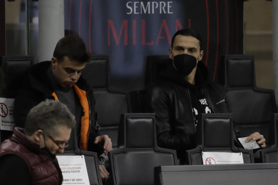 AC Milan's Zlatan Ibrahimovic, right, sits on the stands ahead of a Serie A soccer match between AC Milan and Napoli, at the San Siro stadium in Milan, Italy, Sunday, March 14, 2021. (AP Photo/Luca Bruno)