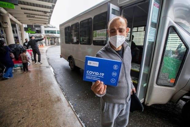 A traveller who arrived at Toronto's Pearson International Airport in February displays an at-home COVID-19 test kit given to all international arrivals before boarding a shuttle bus for a quarantine hotel.