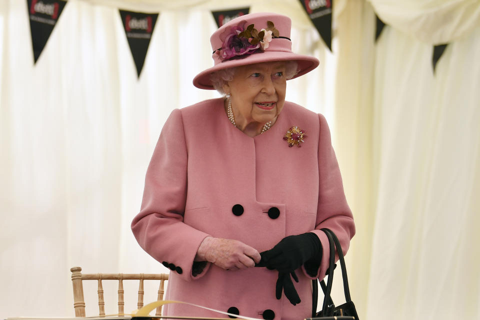 SALISBURY, ENGLAND - OCTOBER 15: Britain's Queen Elizabeth II stands after signing a visitor's book during her visit to the Defence Science and Technology Laboratory (Dstl) at Porton Down science park on October 15, 2020 near Salisbury, England. The Queen and the Duke of Cambridge visited the Defence Science and Technology Laboratory (Dstl) where they were to view displays of weaponry and tactics used in counter intelligence, a demonstration of a Forensic Explosives Investigation and meet staff who were involved in the Salisbury Novichok incident. Her Majesty and His Royal Highness also formally opened the new Energetics Analysis Centre. (Photo by Ben Stansall - WPA Pool/Getty Images)