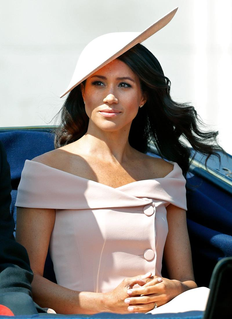 Meghan Markle crosses her hands and looks solemn in a pink dress and hat at the Tropping of the Colour