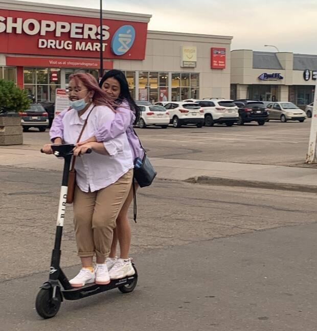 'Doubling up' on e-scooters is not permitted, nor are riders under 18 or riding on sidewalks.   (Natasha Riebe/CBC - image credit)