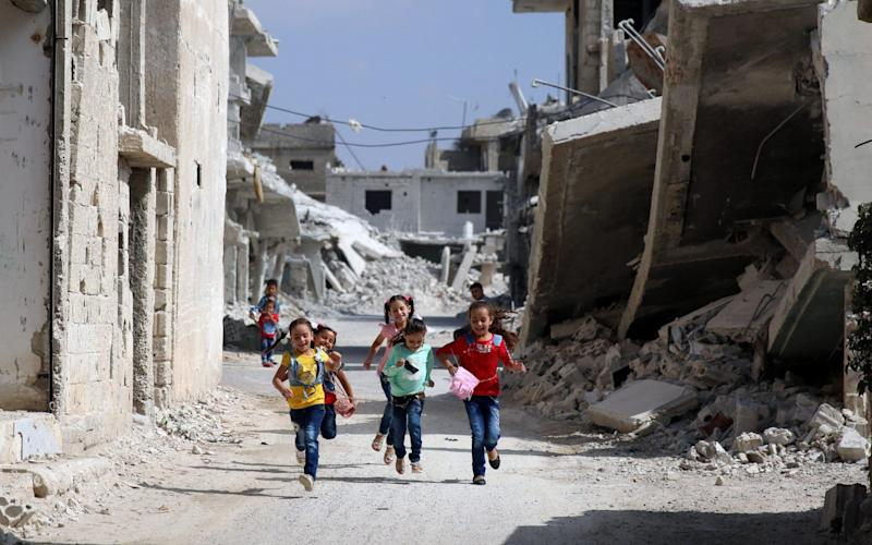Children run along a damaged street as they celebrate the first day of the Muslim holiday of Eid al-Adha in Deraa when it was under the control of rebels - REUTERS