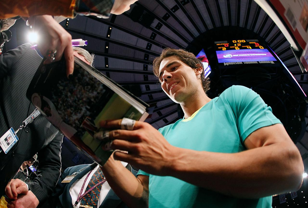 NEW YORK, NY - MARCH 04:  Rafael Nadal of Spain signs autographs following the match against Juan del Potro of Argentina during the BNP Paribas Showdown at Madison Square Garden on March 4, 2013 in New York City.  (Photo by Mike Stobe/Getty Images for StarGames)