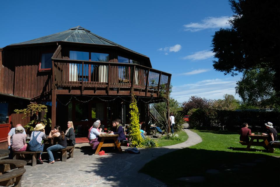 FORRES, SCOTLAND - MAY 14: People sit outside the Community Centre building at Findhorn Foundation's Park Ecovillage on May 14, 2018 in Forres, Scotland, United Kingdom. The Findhorn Foundation has two main sites: The Park next to Findhorn Village and Cluny Hill in Forres. The foundation is a spiritual community, an ecovillage and a learning centre, offering a broad range of holistic workshops and events, as they work in co-creation with the intelligence of nature.  (Photo by Yuriko Nakao/Getty Images)