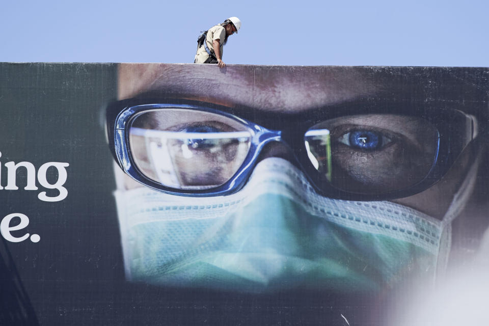 A worker stands atop a billboard showing a medical worker wearing a mask, in Omaha, Neb., Monday, July 27, 2020. Nebraska's online virus tracker on Monday showed 800 cases were confirmed Friday through Sunday, bringing the state's total to 24,618 since the outbreak began. That included 356 cases confirmed on Friday, 221 on Saturday and 223 on Sunday. (AP Photo/Nati Harnik)