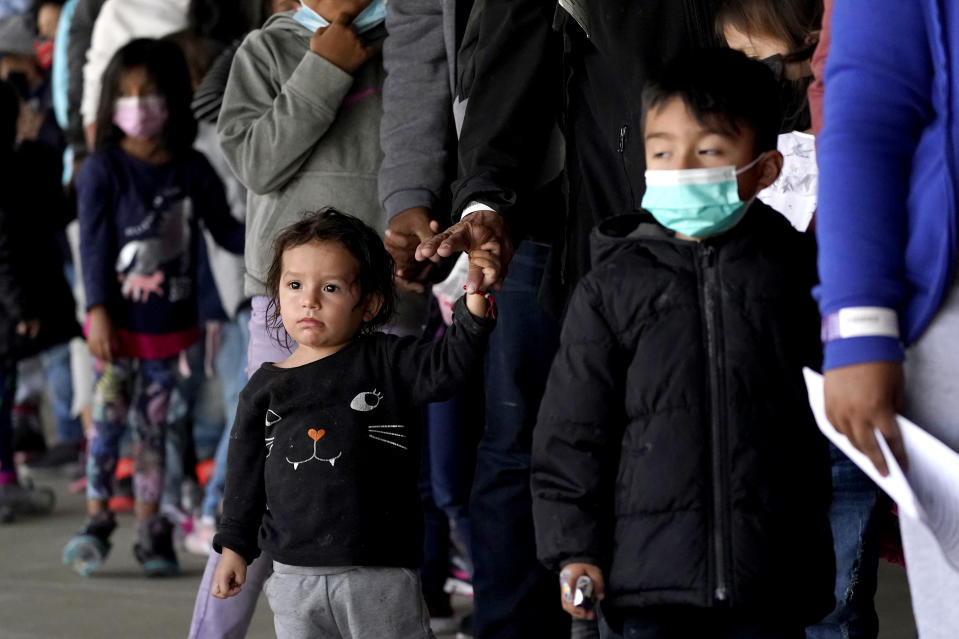Migrant children are seen with adults as they wait in line to get a COVID-19 test before given travel instructions at a bus station, Wednesday, March 17, 2021, in Brownsville, Texas. A surge of migrants on the Southwest border has the Biden administration on the defensive. The head of Homeland Security acknowledged the severity of the problem Tuesday but insisted it's under control and said he won't revive a Trump-era practice of immediately expelling teens and children. An official says U.S. authorities encountered nearly double the number children traveling alone across the Mexican border in one day this week than on an average day last month. (AP Photo/Julio Cortez)