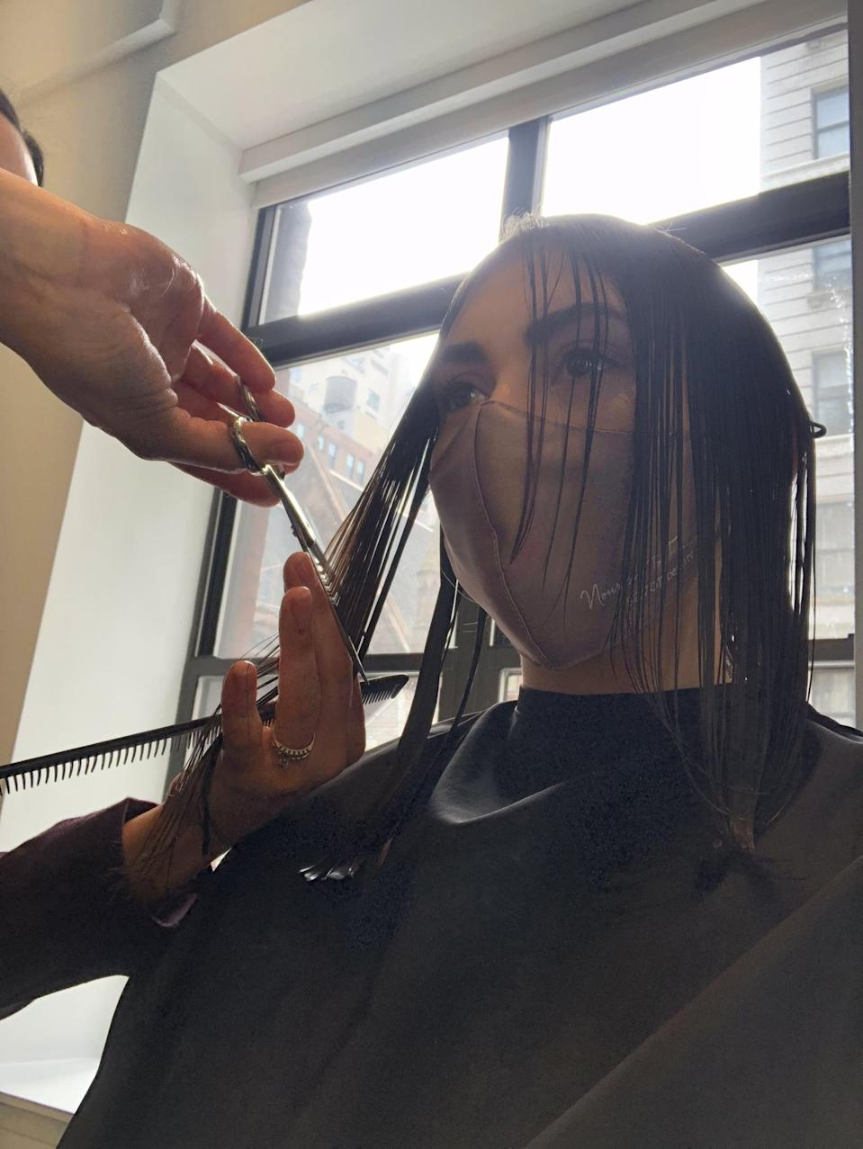 """<p>I wanted to keep most of the length so Santos only trimmed it about an inch to get rid of dead ends before adding long layers to the back of my head. Then it was time to cut the face-framing pieces. With my <a href=""""https://www.popsugar.com/beauty/middle-hair-part-editor-experiment-48192021"""" class=""""link rapid-noclick-resp"""" rel=""""nofollow noopener"""" target=""""_blank"""" data-ylk=""""slk:hair in a middle part"""">hair in a middle part</a> - because I'm <a href=""""https://www.popsugar.com/beauty/middle-part-side-part-debate-48185478"""" class=""""link rapid-noclick-resp"""" rel=""""nofollow noopener"""" target=""""_blank"""" data-ylk=""""slk:a cool Gen Zer"""">a cool Gen Zer</a>, if you couldn't tell - she cut the hair on either side of my face using a downward angle. The shortest pieces hit right at my cheekbones and gradually faded into the rest of my hair. She said the hairstyle was """"easy to manage and style,"""" which was music to my ears.</p>"""