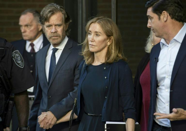Actress Felicity Huffman, shown leaving Boston's federal courthouse on September 13, 2019 escorted by her husband William H. Macy, had pleaded guilty to paying $15,000 to boost her daughter's SAT college entrance exam score