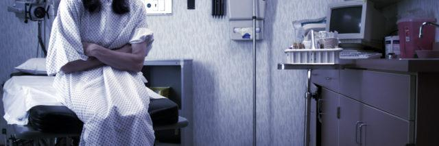 a woman sitting in a doctor's office, waiting to be examined