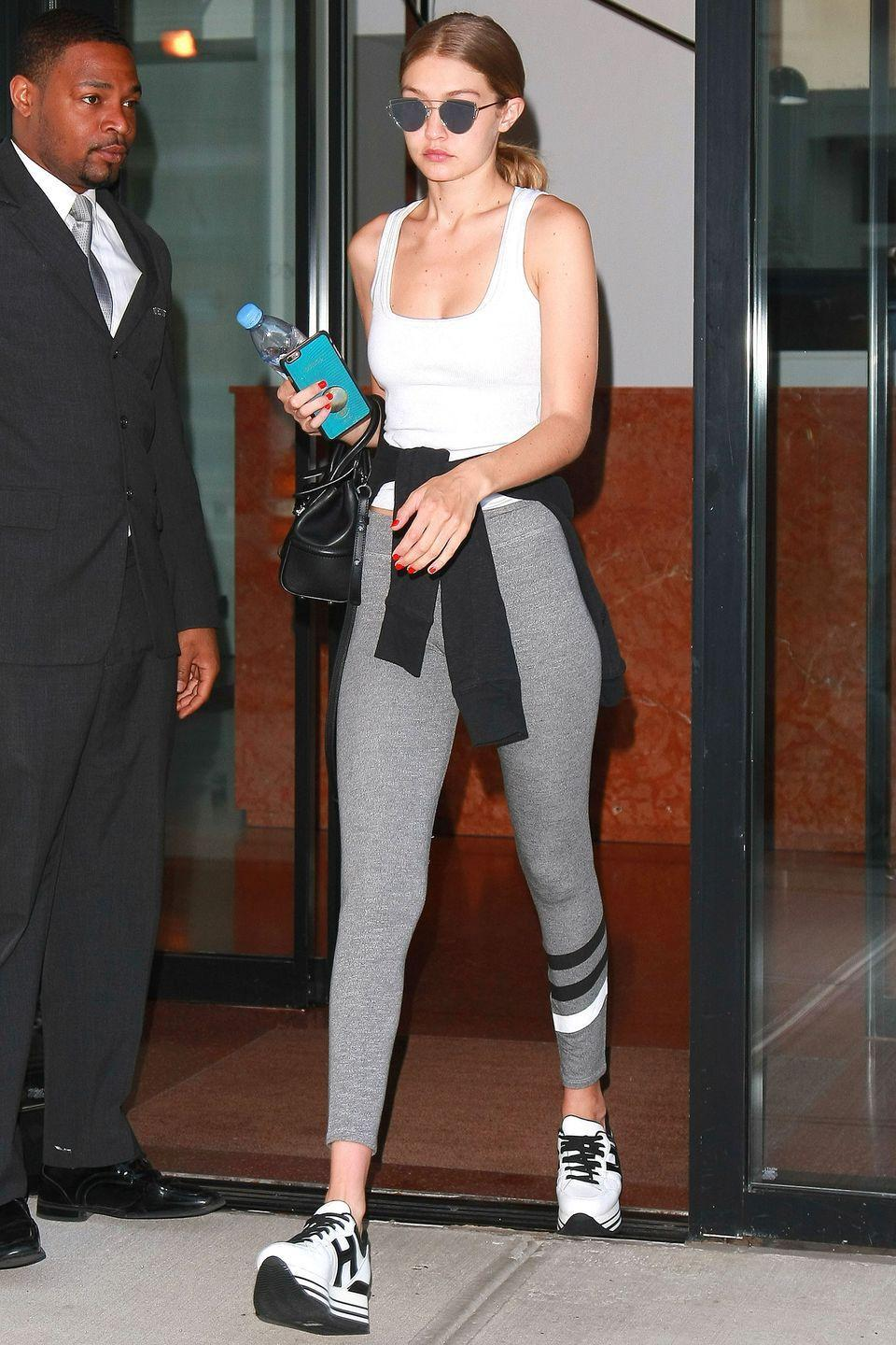 <p>In a white tank top, grey striped leggings, platform sneakers, a black leather handbag, Gentle Monster reflective sunnies and a black sweatshirt wrapped at the waist. </p>