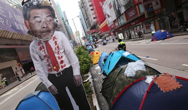 Protesters along the streets in Hong Kong on 2014, with a sign showing the face of then city leader CY Leung. Photo: Felix Wong