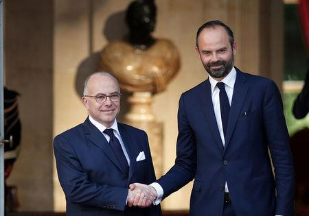 Newly-appointed French Prime Minister Edouard Philippe is greeted by his predecessor Bernard Cazeneuve during a handover ceremony at the Hotel Matignon, in Paris