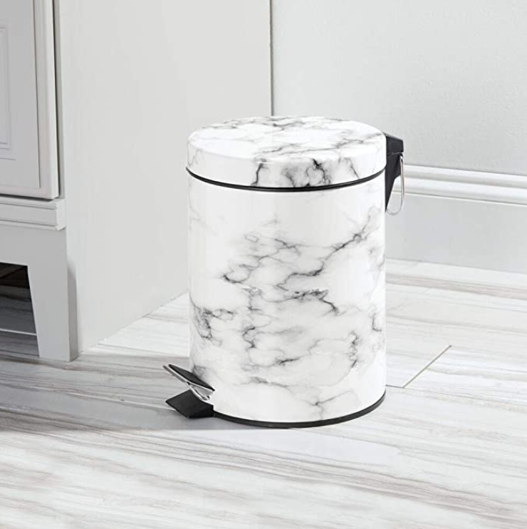 """<h3>Marble-Print Step Wastebasket</h3><br>Even though it's only a marble-patterned print, this sleek wastebasket still radiates """"welcome to my luxury kitchen"""" style. <br><br><strong>mDesign</strong> Round Small Step Trash Can, $, available at <a href=""""https://amzn.to/3y7Gc1E"""" rel=""""nofollow noopener"""" target=""""_blank"""" data-ylk=""""slk:Amazon"""" class=""""link rapid-noclick-resp"""">Amazon</a>"""