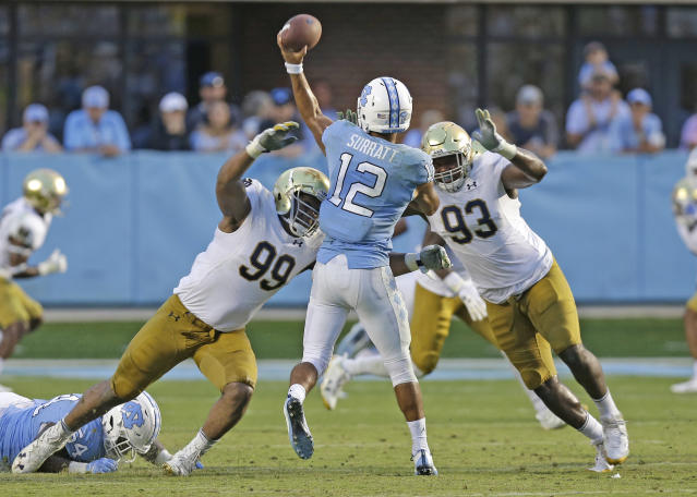 """Notre Dame's <a class=""""link rapid-noclick-resp"""" href=""""/ncaaf/players/252140/"""" data-ylk=""""slk:Jerry Tillery"""">Jerry Tillery</a> (L) and Jay Hayes (R) rush North Carolina quarterback Chazz Surratt (C) during the second half of an NCAA college football game in Chapel Hill, N.C., Saturday, Oct. 7, 2017. Notre Dame won 33-10. (AP)"""