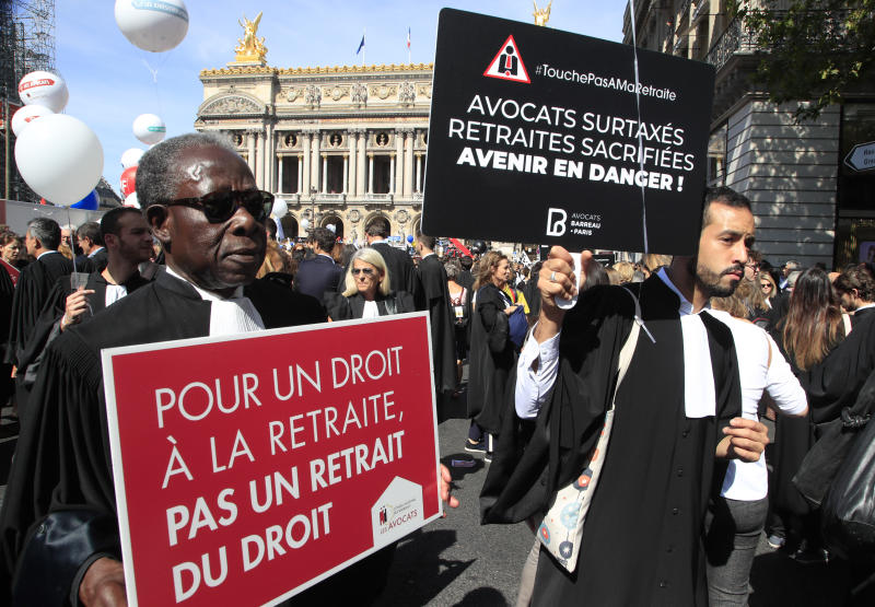 """Lawyers march with placards during a protest against the planned pension change in Paris, Monday, Sept. 16, 2019. French lawyers, doctors, nurses, pilots and others are taking to the streets of Paris to protest planned pension changes by French President Emmanuel Macron's government. Placards read, """"to have the right on pension and not a pension of law"""", left, """"lawyers over taxed, pension scarified, future in danger"""". (AP Photo/Michel Euler)"""