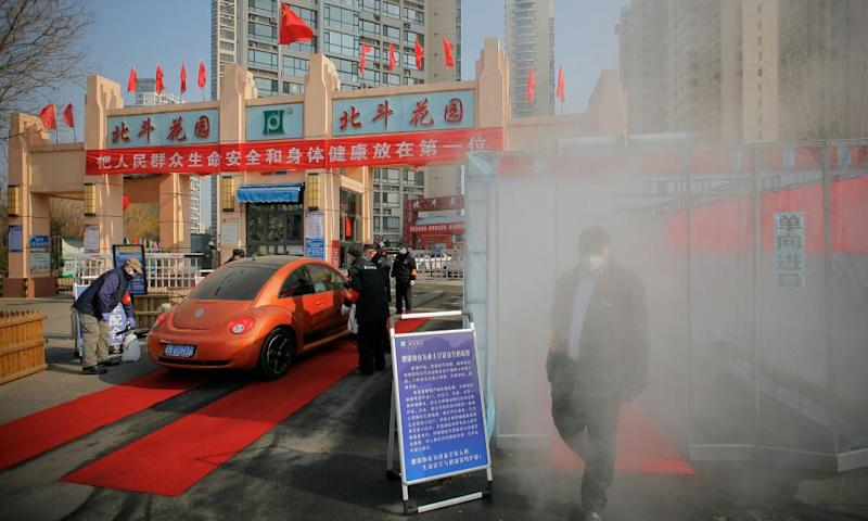 Disinfectant sprayed on people entering a residential compound in Tianjin, China