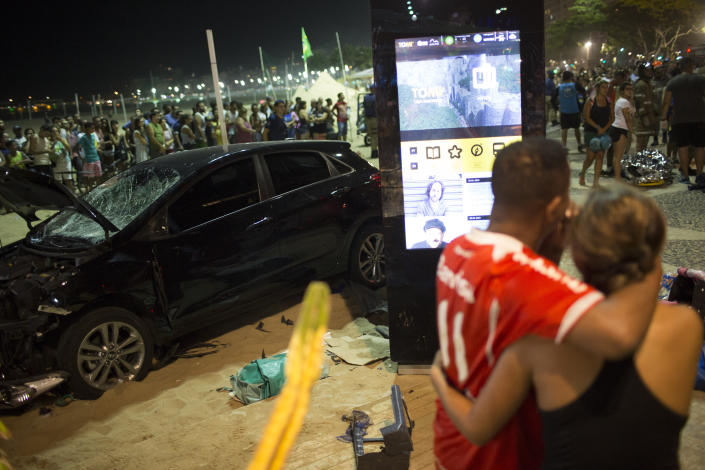 <p>People watch the site of the accident where a car that has driven into the crowded seaside boardwalk along Copacabana beach in Rio de Janeiro, Brazil, Thursday, Jan. 18, 2018. (Photo: Silvia Izquierdo/AP) </p>
