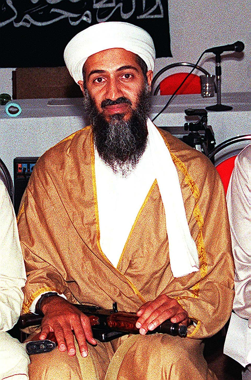 AFGHANISTAN:An undated file picture shows Osama Bin Laden attending a meeting with a Kalashnikov on his lap in an undisclosed place inside Afghanistan. Bin Laden is reported to have been funding the Abu Sayyaf, who are currently holding over a dozen hostages in the southern Philippine island of Jolo, through a Islamic charity, the International Islamic Relief Organisation (IIRO) which he set up in 1992 with his brother-in-law Mohammad Jamal Khalifa as a front for funding extremist groups. Bin Laden, a wealthy Saudi dissident living in Afghanistan, is wanted by the United States for masterminding a terrorist attack on tow US embassies in east Africa in 1998 which killed 224 people. AFP PHOTO/FILES (Photo credit should read AFP via Getty Images)