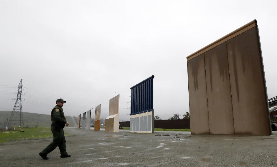 FILE - In this Feb. 5, 2019 file photo, U.S. Border Patrol agent Vincent Pirro walks towards prototypes for a border wall in San Diego. The Biden administration says it will begin work to address flooding and soil erosion risks from unfinished walls on the U.S. border with Mexico. It also began providing answers on how it will use unspent money from shutting down one of President Donald Trump's signature domestic projects. The Defense Department says it will use unobligated money for military construction projects for its initial purpose. (AP Photo/Gregory Bull, File)