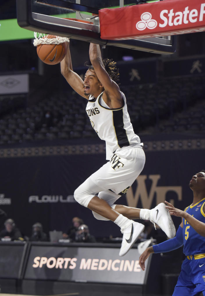 Wake Forest's Jalen Johnson gets past Pittsburgh's Au'diese Toney for a dunk during an NCAA college basketball game Saturday, Jan. 23, 2021, in Winston-Salem, N.C. (Walt Unks/The Winston-Salem Journal via AP)